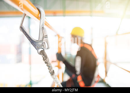 Industrial Worker with safety protective equipment loop hanging on the bar besides, safety concept - Stock Photo