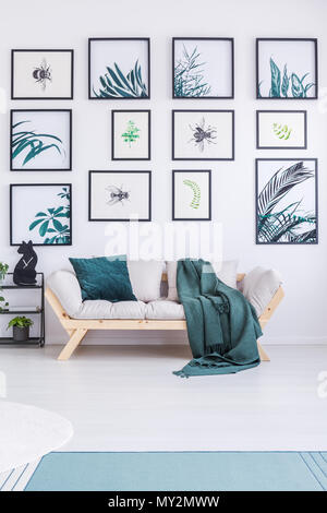 Real photo of a couch standing next to a wall full of botanic paintings in a simple living room interior - Stock Photo