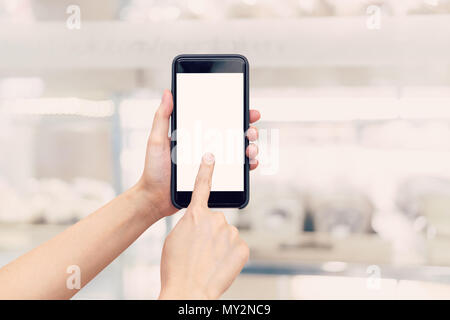 hand woman holding phone with blank screen and blur shopping mall.