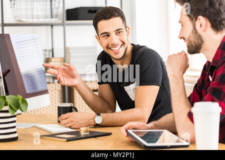 Handsome man showing something on a computer to his colleague in office - Stock Photo