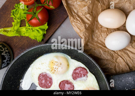 fried eggs on pan with salami, tomatoes, letucce. Health English breakfast. - Stock Photo