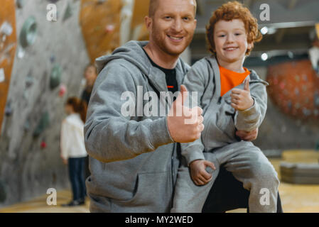 Half-length shot of smiling dad with son sitting on his knee showing thumbs up - Stock Photo