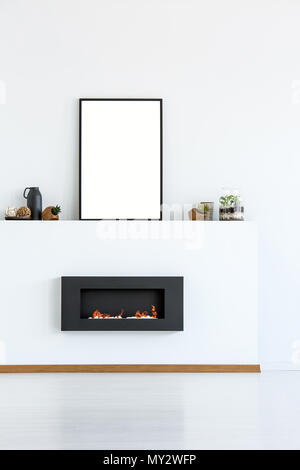 Mockup of empty poster above black fireplace in simple white living room interior. Real photo with a place for your graphic - Stock Photo