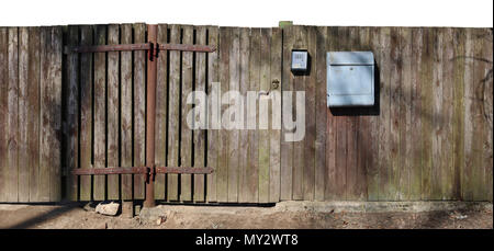 Crooked ugly wooden rural aged fence  with mail box isolated on top. Sunny spring day panoramic shot - Stock Photo