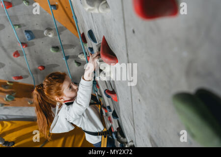 High angle shot of little girl in a harness climbing a wall with grips at gym - Stock Photo