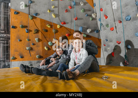 Family with children sitting on a mat at gym with climbing walls in the background - Stock Photo