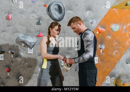 Half-length shot of young man and woman in sportive attire applying talcum powder to their hands from a bag - Stock Photo