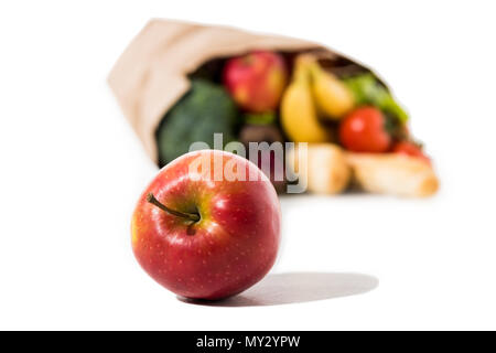 close-up view of ripe red apple and full grocery bag isolated on white - Stock Photo