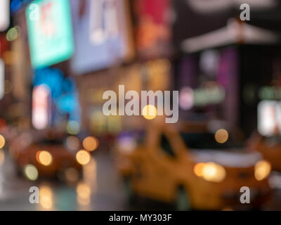 A deliberately defocused shot of yellow taxi cabs zooming through Times Square, New York City with neon signs in the background - Stock Photo