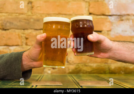 Friends at the bar table holding two pints of beer, cheers - Stock Photo