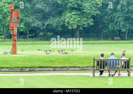 A trio of students sit on a bench by the river Cam during a sunny summer day on the lawn outside the Wren library at Trinity college, university of Ca - Stock Photo