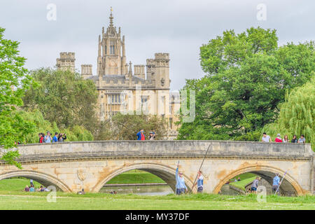 Tourists take photos from Trinity bridge while others punt along the river Cam next to Trinity college, university of Cambridge, England, with St John - Stock Photo