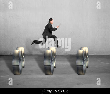 Businessman jumping over money symbols on concrete background - Stock Photo