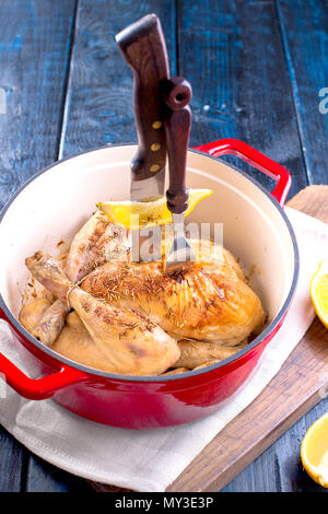 a cast-iron pot and a golden chicken with lemon and rosemary from the oven. Delicious family dinner. Place for text. copy space - Stock Photo