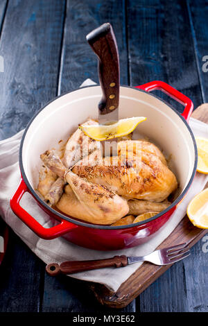 a cast-iron pot and a golden chicken with lemon and rosemary from the oven. Delicious family dinner. Place for text. copy space. - Stock Photo