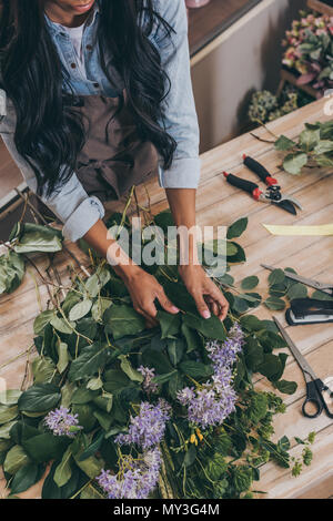 cropped shot of young african american woman arranging flowers and green leaves in flower shop - Stock Photo