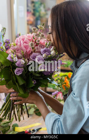young african american woman smelling beautiful flowers in flower shop - Stock Photo