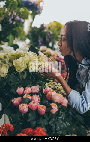 young african american woman smelling beautiful roses in flower shop - Stock Photo