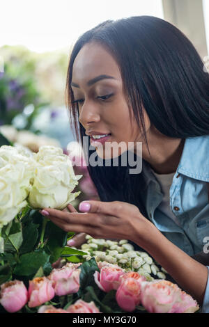 beautiful young african american woman smelling roses in flower shop - Stock Photo