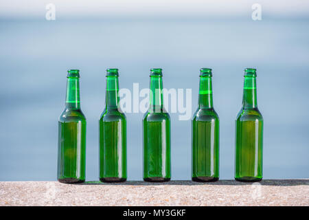 close up view of bottles of beer standing in line on parapet - Stock Photo