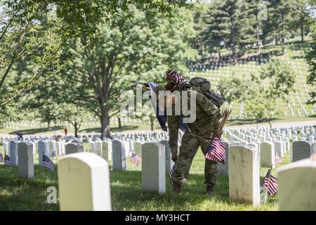 A Soldier from the 3d U.S. Infantry Regiment (The Old Guard) places U.S. flags at headstones in Section 43 during Flags In at Arlington National Cemetery, Arlington, Virginia, May 24, 2018, May 24, 2018. For more than 60 years, Soldiers from the Old Guard have honored our nation's fallen heroes by placing U.S. flags at gravesites for service members buried at both Arlington National Cemetery and the U.S. Soldiers' and Airmen's Home National Cemetery just prior to the Memorial Day weekend. Within four hours, more than 1, 000 Soldiers placed 234, 537 flags in front of every headstone and Columba - Stock Photo