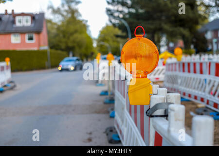 red and white barricades with warning lights at a street in the residential zone, depth of field - Stock Photo