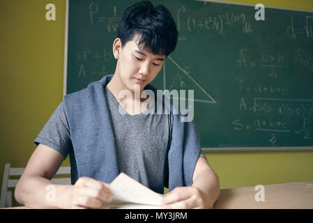 Young man studying in math class - Stock Photo