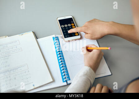Students using smartphone calculator function while completing math assignment - Stock Photo