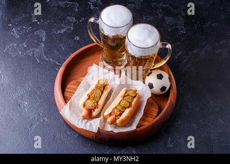 Photo on top of two glasses of beer and hot dogs on wooden tray with football - Stock Photo