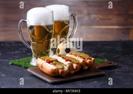 Photo of two mugs of foam beer, green grass with football, hotdogs - Stock Photo