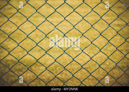 Wire fence with yellow grass on background - Stock Photo