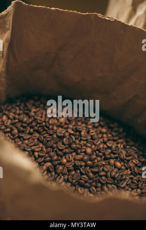close up view of coffee beans in paper bag - Stock Photo