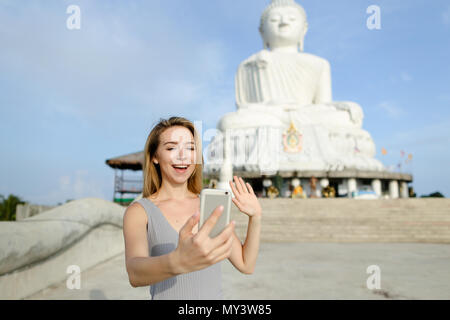 Young girl making video call by smartphone and showing Buddha white statue in Phuket. - Stock Photo