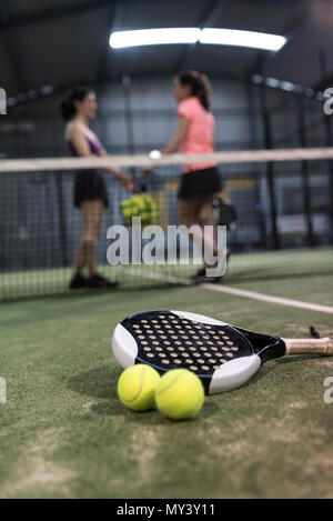 Paddle tennis objects on turf ready for tournament and women in background - Stock Photo