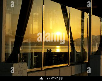 Reflection of sunset on restaurant windows - Stock Photo
