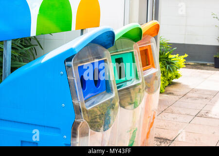 Close up yellow, green, blue recycle bins with recycle symbol in the park. - Stock Photo