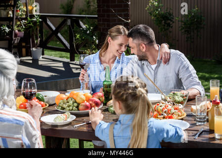 portrait of smiling man and woman sitting at table with family near by - Stock Photo