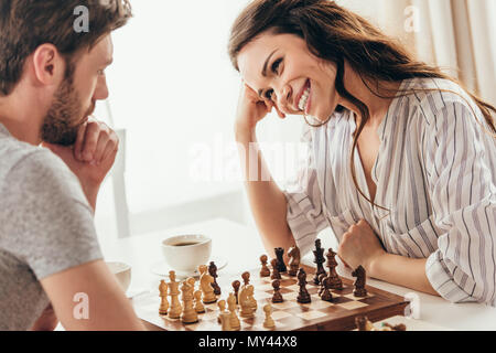 young couple playing chess while sitting at table at home - Stock Photo
