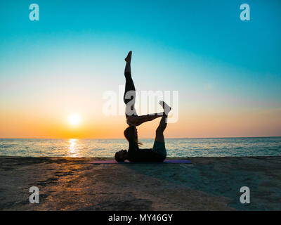 Young beautiful couple practicing acro yoga on the sea beach near water. Man and woman doing everyday practice outdoor on nature background. Healthy l - Stock Photo