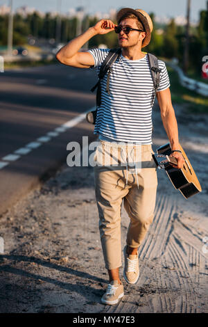 young man with guitar walking along road while hitchhiking alone - Stock Photo