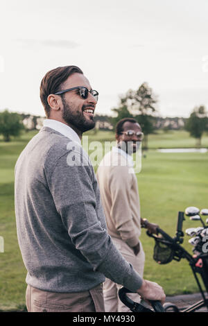 Two smiling men in sunglasses holding golf clubs in bags and talking outdoors - Stock Photo