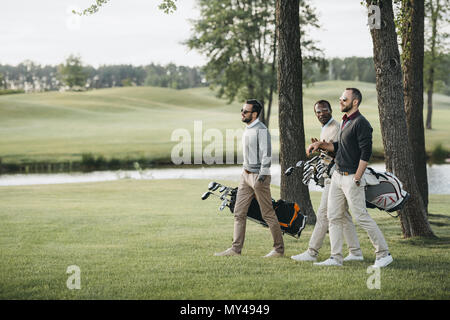 multiethnic golf players holding bags with golf clubs and walking on golf course - Stock Photo