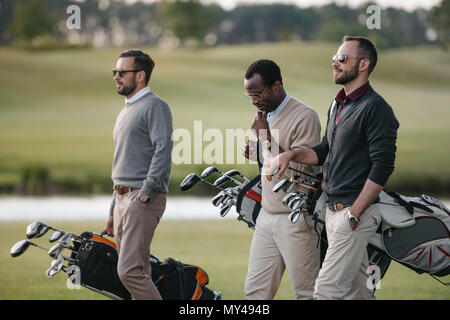 multiethnic golfers holding bags with golf clubs and walking on golf course - Stock Photo