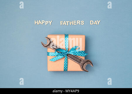 Happy Father's day card with gift box wrapped in kraft paper tied with blue ribbon in polka dots and wrench on blue grey background. Greeting card with wooden letters. - Stock Photo