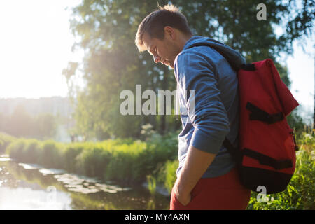 Man with red backpack walking in forest near river alone. - Stock Photo