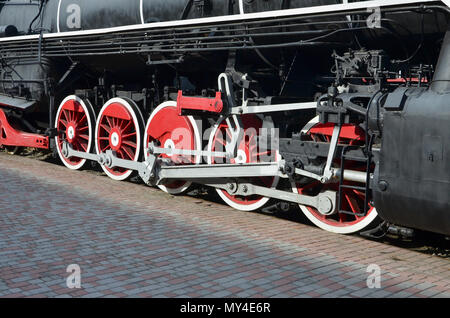 Wheels of the old black steam locomotive of Soviet times. The side of the locomotive with elements of the rotating technology of old trains - Stock Photo