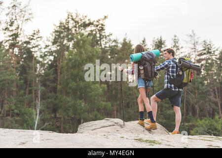 young hikers with backpacks standing on cliff and looking away - Stock Photo