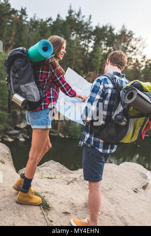 active couple with backpacks looking at map near mountain lake - Stock Photo
