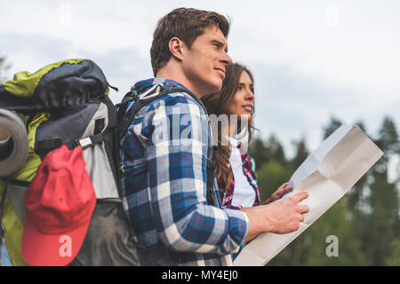 thoughtful active couple of hikers with map looking away - Stock Photo