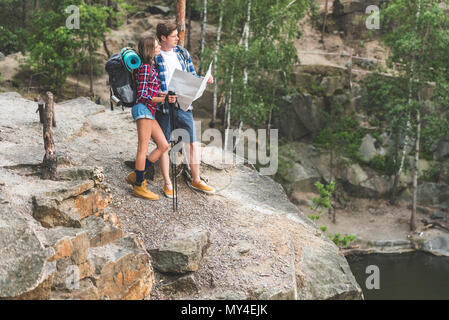 hiking couple with map looking at mountain lake - Stock Photo